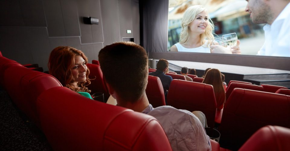 Kino, Jena, cinema, entertainment, communication and people concept - happy couple of friends watching movie and talking in theater from back
